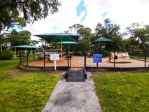 Playground in a city park in Sarasota Florida. Child`s playground with green tin roof under a bright blue sunny sky stock image
