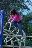 Playground Climber. Young girl scaling playground equipment royalty free stock image