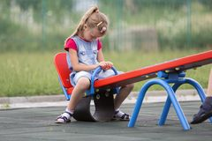 Playground conflicts. Small cute young blond child girl sits moody, angry and offended on see- saw swing on bright green blurred b. Ackground. Joys and sorrows stock photos