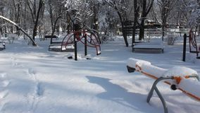 Playground covered in snow. Children's playground in the park covered by snow stock video footage