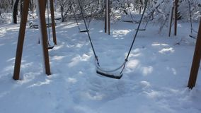 Playground covered in snow - swing. Children's playground in the park covered by snow stock footage