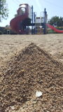 Playground in distance. Sand in playground with climbing structure and slide in background Stock Photography