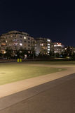 Playground in empty park at night with residential buildings Stock Photo