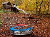 Playground in forest at fall. Playground with a merry-go-round and a slide in a forest by a wet day at fall Stock Images