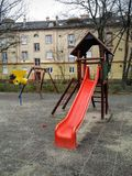 Playground. In front of a block of flats.  Red slide and jungle gym. Yellow house in the background Royalty Free Stock Photos
