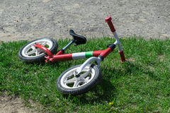 On the playground the grass is a children`s balance bike. Royalty Free Stock Photography