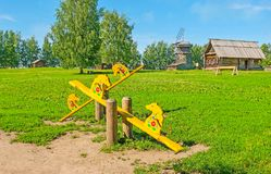 The horse seesaws in Suzdal. The playground on the green meadow with traditional Russian horse seesaws, decorated with floral patterns and located in Suzdal Stock Image