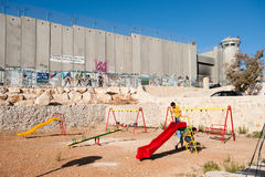 Playground and Israeli Separation Wall. BETHLEHEM, OCCUPIED PALESTINIAN TERRITORIES - SEPTEMBER 19: In a playground next to the Israeli separation wall dividing Royalty Free Stock Images