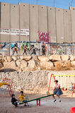 Playground and Israeli Separation Wall. BETHLEHEM, OCCUPIED PALESTINIAN TERRITORIES - SEPTEMBER 19: In a playground next to the Israeli separation wall dividing Stock Photo
