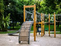 Playground for kid in the public park. Multi station wooden playground. with slide, climb and hang Stock Photo