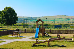 Playground for the kids in a large open space. A children's playground with kids playing soccer in the background Royalty Free Stock Image