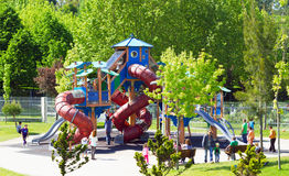 Playground. A playground on a leafy and colorful public park with happy young kids having fun during a bright sunny day stock photos