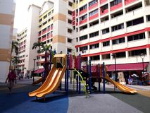 A playground in the middle of two HDB buildings in the town of Tampines, Singapore. TAMPINES, SINGAPORE - DECEMBER 21, 2015: A playground in the middle of two Stock Image