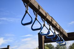 PLAYGROUND MONKEY BARS IN A ROW WITH BLUE SKY. A line of monkey bars unattended on a beautiful blue sky day wait for kids to use them royalty free stock photo