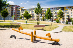 Playground in nature in front of row of newly built block of flats Stock Image