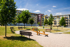 Playground in nature in front of row of newly built block of flats Royalty Free Stock Photos