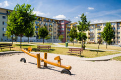 Playground in nature in front of row of newly built block of flats Royalty Free Stock Photography
