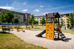 Playground in nature in front of row of newly built block of flats Stock Photo
