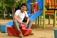 Playground at the park. Man playing rocking horse in the playground Royalty Free Stock Image