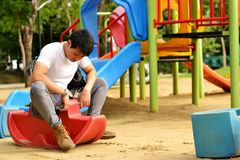 Playground at the park. Man playing rocking horse in the playground Royalty Free Stock Images