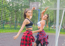 On the Playground posing beautiful girls at the football grid. Two sporty girls posing at a football grid on the Playground Stock Photos