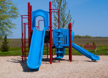 Playground Red and Blue Slide Climbing Structure Park. A red and blue playground with a slides and climbing structures Stock Photography
