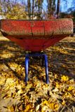 A playground with a red shawl for two children. Old peeling paint, sunny golden autumn. royalty free stock images