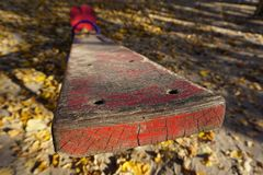 A playground with a red shawl for two children. Old peeling paint, sunny golden autumn. stock photo