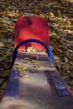 A playground with a red shawl for two children. Old peeling paint, sunny golden autumn. stock photography