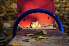 A playground with a red shawl for two children. Old peeling paint, sunny golden autumn. stock images