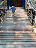 Playground rope bridge. A child crossing rope bridge in playground Royalty Free Stock Images