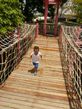 Playground rope bridge. A child crossing rope bridge in playground Stock Photos