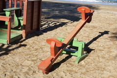 Playground seesaw. Teeter-totter or teeterboard is a long, narrow board supported by a single pivot point, most commonly located at the midpoint between both Stock Photo