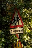 Playground Sign post. Playground Warning, Sign post, in foliage, plant leaves Royalty Free Stock Images