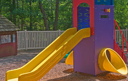 Playground slide. Colorful children's playground equipment at a daycare center in the woods with a closeup view of a kid's slide Stock Photography