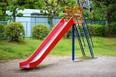 Playground slide. Red playground slide in the park Royalty Free Stock Photo