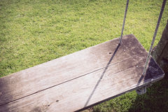 Playground swing hanging in green grass field Royalty Free Stock Photography