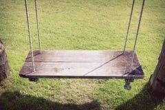 Playground swing hanging in green grass field Stock Photo
