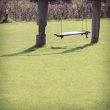 Playground swing made wood hanging in green grass Royalty Free Stock Photo