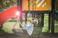 Playground swing set with lens flare (selective focus) Stock Photo