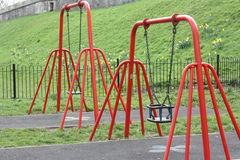 Empty swings. Two swings supported on brown painted iron structures in the park, one swing green designed to be safe for babies and the other a simple wooden Royalty Free Stock Photos