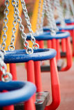 Playground swings. Kids and babies entertainment at parks Stock Images