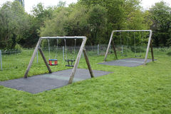 Playground swings. A set of children's swings in a playground Royalty Free Stock Image