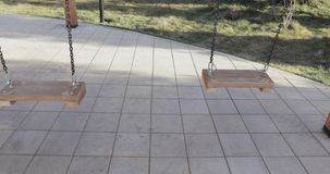 Swing swing on a chain. On the playground, a wooden swing is swinging on a chain. Man sit down and ride stock footage
