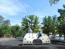 At The Playground. A young girl and her father playing on climbing equipment at the playground stock photography