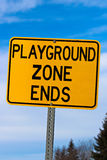 Playground Zone End Sign Against Blue Cloudy Sky and Trees Royalty Free Stock Image