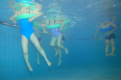 Playing. Underwater picture of children playing in the swimming-pool Stock Photos