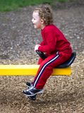 Playing. Young boy riding on see-saw outdoors at playground Royalty Free Stock Photo