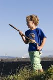 Playing. A boy plays beside an old concrete bunker with a stick for a gun Royalty Free Stock Image