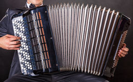 Playing the accordion. Close-up musician playing the accordion against a black background stock image